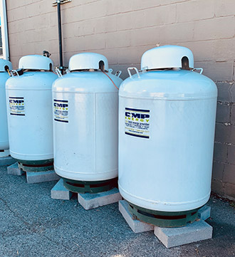 picture of white propane tanks lined up against wall